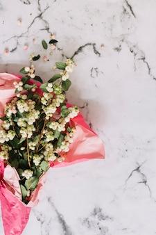 Symphoricarpos albus; galhos snowberry comuns embrulhados em papel rosa no pano de fundo de mármore