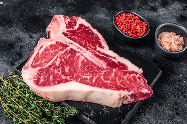 T-bone cru envelhecido a seco ou carne bovina porterhouse bife com ervas e sal. fundo preto. vista do topo.