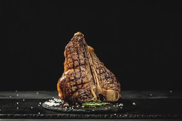 T-bone steak grelhado ou bife porterhouse com alecrim fresco. cozinha americana. menu do restaurante, dieta, receita do livro de receitas. o conceito de pral cozinhar carne.