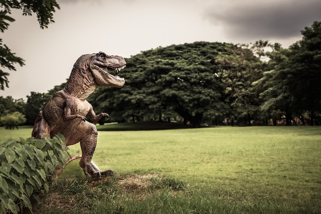 T-rex com galhos de árvores contra a natureza