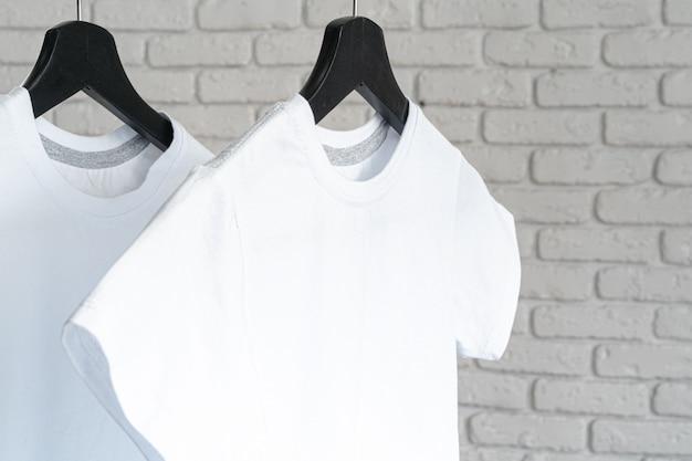 T-shirt branca pendurada no cabide contra a parede de tijolos, copie o espaço
