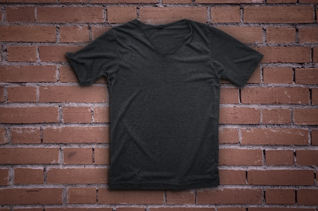 T-shirt cinzento no fundo da parede de tijolo.