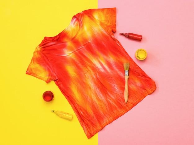 T-shirt da moda no estilo tie dye com tintas e pincéis sobre superfície colorida. tecido tingido em estilo tie dye. postura plana.