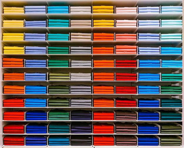 T-shirt de cor diferente são ordenadamente empilhados em uma fileira nas prateleiras da loja.