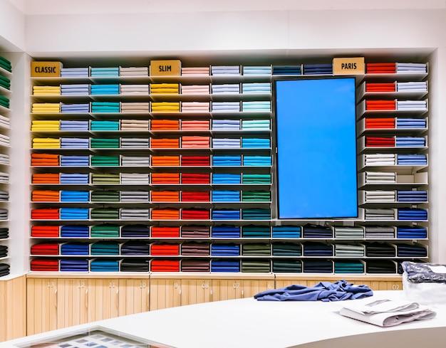 T-shirt de cores diferentes são ordenadamente empilhados em uma fileira nas prateleiras da loja em torno de tela promocional
