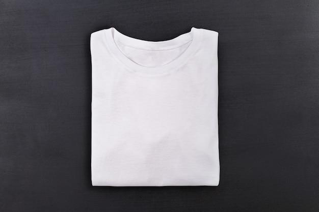 T-shirt dobrada branca sobre fundo preto lousa