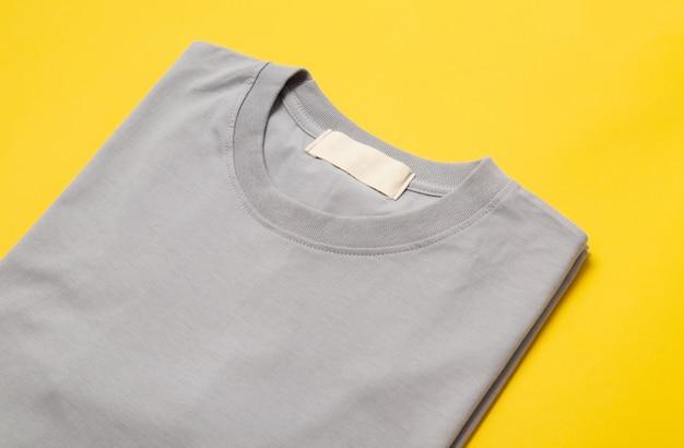 T-shirt dobrada cinza com tag em branco para seu projeto isolado em amarelo