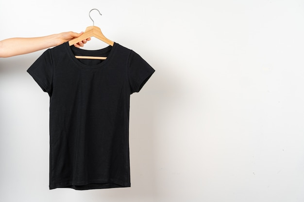 T-shirt lisa preta pendurada num cabide, copie o espaço