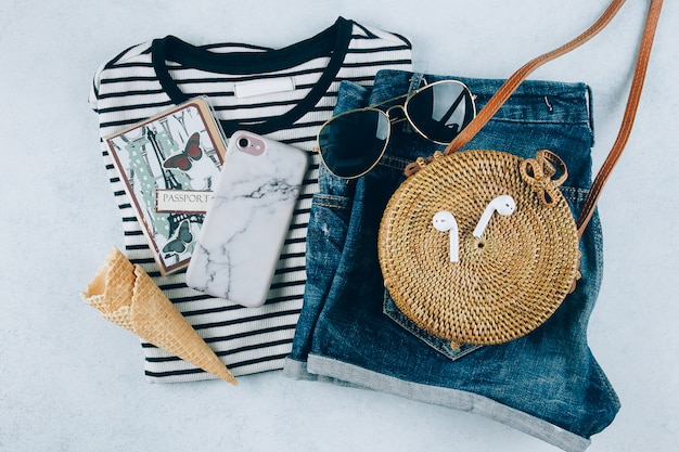 T-shirt listrada, calções de ganga azul, elegante saco de rattan orgânico. férias, conceito de viagem.