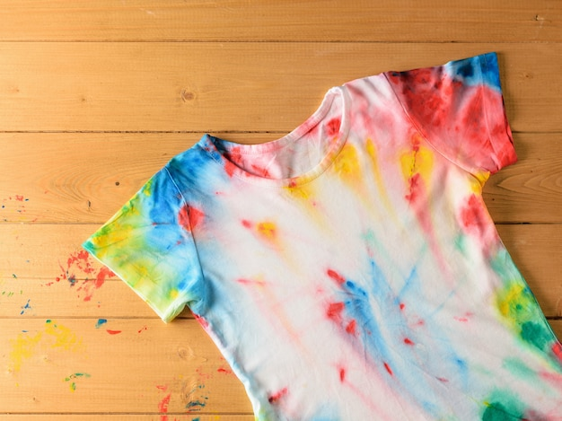 T-shirt no estilo tie dye em uma mesa de madeira clara manchada com tinta