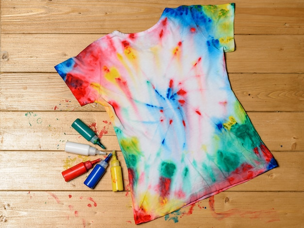T-shirt pintada no estilo tie dye em uma mesa de madeira.