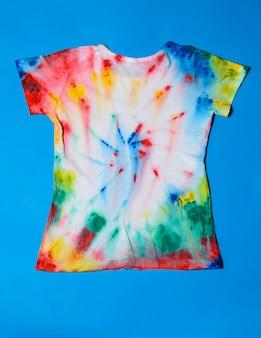 T-shirt pintada no estilo tie dye numa mesa azul