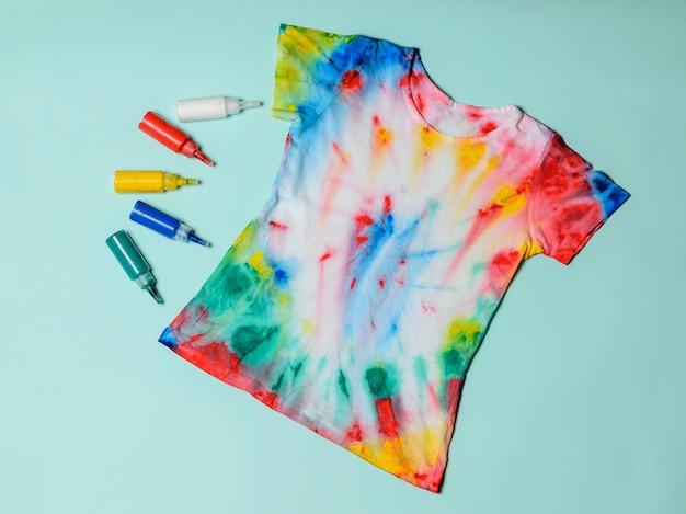 T-shirt pintada no estilo tie dye sobre um fundo azul pastel.