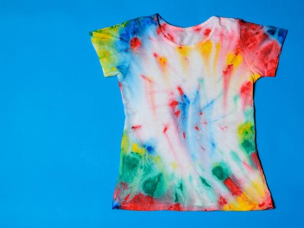 T-shirt pintada no estilo tie dye sobre um fundo azul. postura plana. lugar para texto.