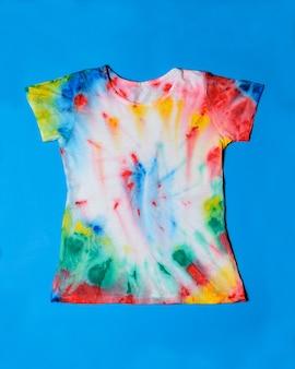 T-shirt pintada no estilo tie dye sobre um fundo azul.