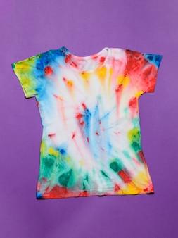 T-shirt pintada no estilo tie dye sobre um fundo roxo.
