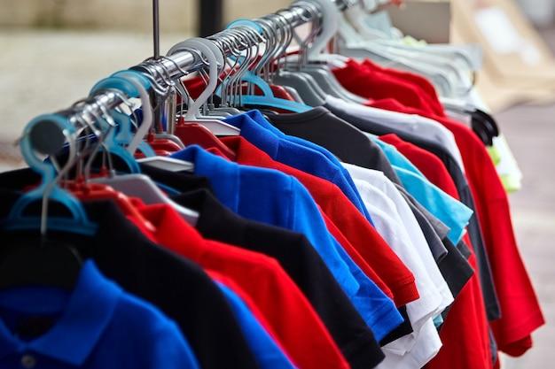 T-shirt polo colorida para o homem em cabides numa loja de retalho