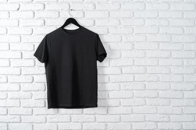 T-shirt preta pendurada em um cabide contra a parede de tijolos, vista frontal