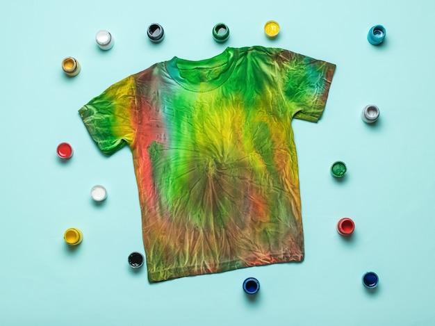 T-shirt tie dye lindamente decorada com cores sobre fundo azul. postura plana.