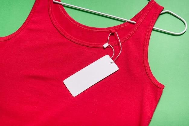T-shirt vermelha nas tiras no cabide com etiqueta de papelão