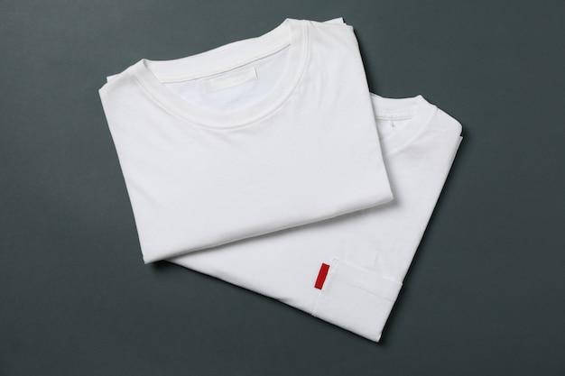 T-shirts brancas dobradas sobre fundo preto claro, espaço para texto