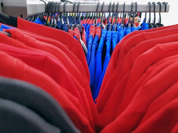 T-shirts coloridas e camisas de polo penduradas nas prateleiras com foco seletivo