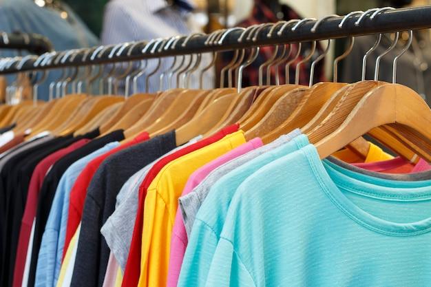 T-shirts multicoloridas com mangas compridas em cabides de madeira, vista lateral.