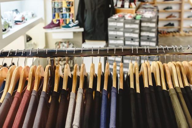 T-shirts penduradas em um rack em uma loja de moda.