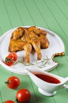Tabaco de frango com molho de tomate, alecrim e tomate em um lindo prato branco sobre uma mesa verde. frango grelhado.