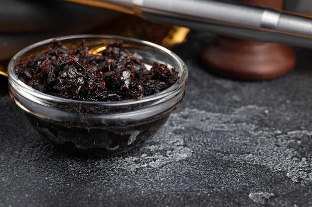 Tabaco para narguilé em uma tigela de vidro na superfície cinza close-up