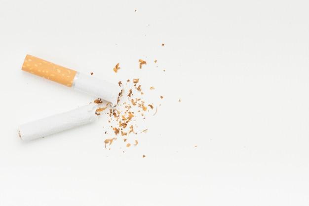 Tabaco vindo do cigarro quebrado contra o pano de fundo branco
