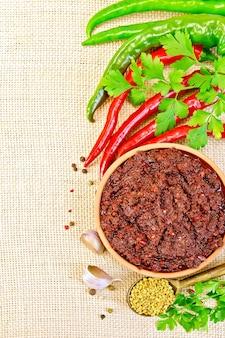 Tabasco adjika em uma xícara de barro, pimenta, alho, salsa, feno-grego no fundo de um pano de saco