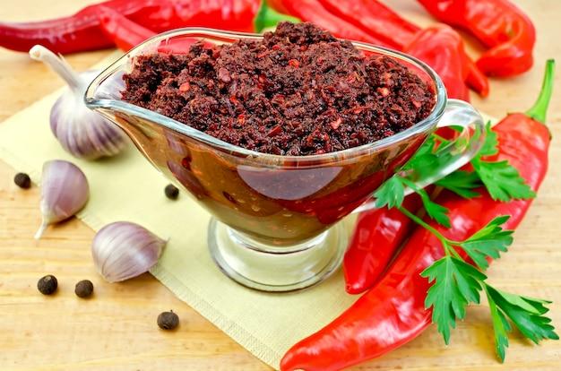 Tabasco em uma molheira de vidro com vagens de pimenta vermelha fresca, um raminho de salsa e alho em um guardanapo amarelo em uma placa de madeira
