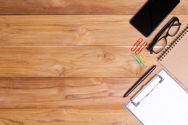 Tabela branca da mesa de escritório com caderno dos monóculos, planta do escritório, pena, grampos e smartphone.
