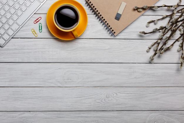 Tabela branca da mesa de escritório com caderno, o computador, fontes e o copo de café vazios. vista superior com espaço de cópia. lay plana.