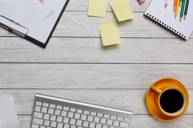 Tabela branca da mesa de escritório com café, teclado do pc de secretária e caderno. vista superior com espaço de cópia. conceito de espaço de mesa.