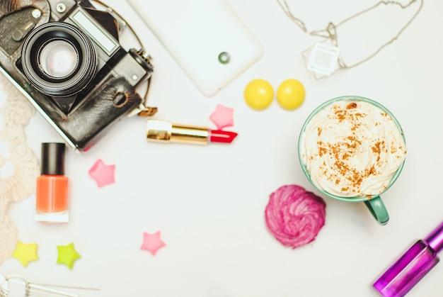 Tabela branca da mesa de escritório com smartphone, câmera do vintage, latte da especiaria e cosméticos.