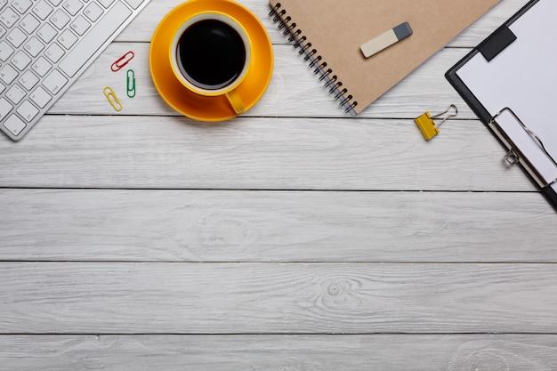 Tabela branca denominada da mesa de escritório da fotografia conservada em estoque com caderno, o teclado, bolinho de amêndoa, fontes e o copo de café vazios. vista superior com espaço de cópia. lay plana.