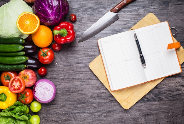 Tabela com legumes, uma faca e um caderno