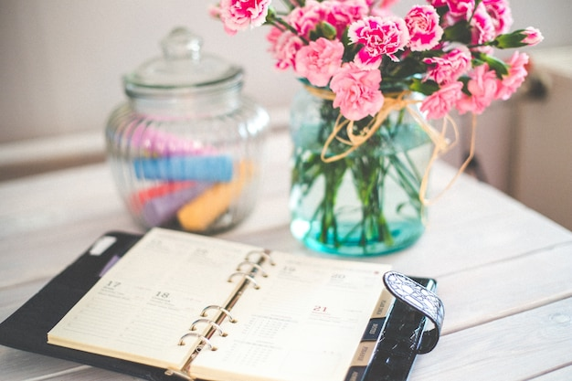 Tabela com vaso de flores e diário