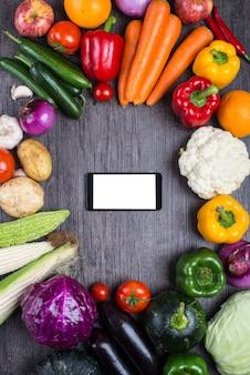 Tabela com vegetais e um telefone móvel