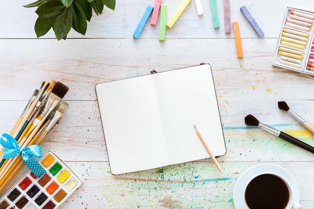 Tabela criativa colorida com caderno em branco para desenhos e tintas, vista superior