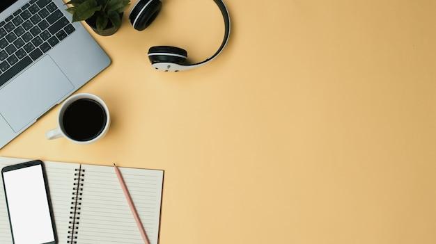 Tabela da mesa do amarelo do espaço de trabalho do escritório com portátil, café, móbil, caderno, planta. colocação plana