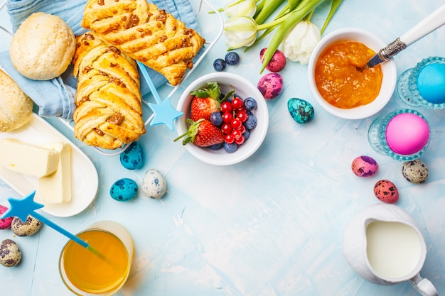 Tabela de café da manhã de páscoa. ovos coloridos, pães, suco e geléia. fundo azul, vista superior, quadro de comida.