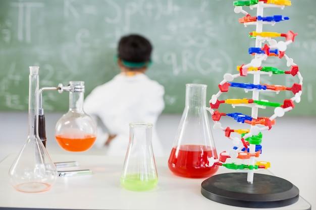 Tabela de copo e frascos de produtos químicos em laboratório
