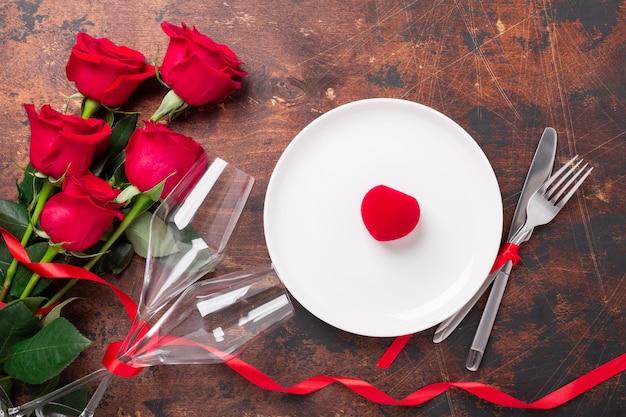 Tabela de dia dos namorados definindo prato vazio, rosas vermelhas, caixa de anel de veludo e taças de champanhe em fundo de madeira