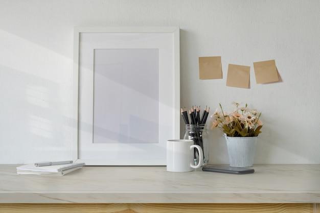Tabela de espaço de trabalho de maquete com quadro de pôster branco