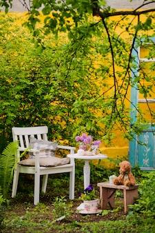 Tabela de madeira branca da cadeira com um ramalhete do jardim dos lilás na primavera.