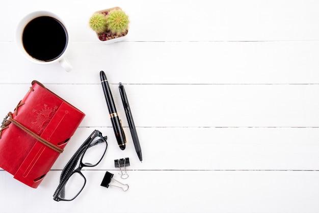 Tabela de madeira branca da mesa de escritório com caderno vermelho, a pena preta, o copo de café e os outros materiais de escritório.