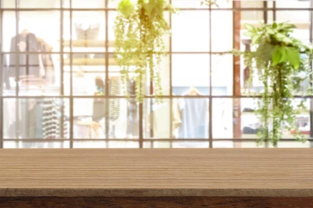 Tabela de madeira branca vazia da perspectiva na parte superior sobre o fundo do borrão.